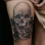 Realistic black and grey skull and rose tattoo by Ethan Jones